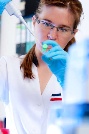 Serious female scientist takes aliquote from enzyme tube photo