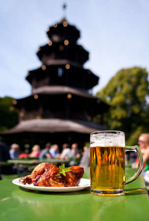 Mug of beer and half chicken against Pgoda in English Garden, Munich, Bavaria, Germany photo