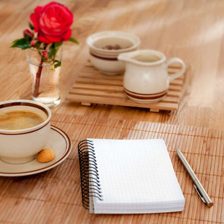 Notebook with pen and morning coffee in cafe
