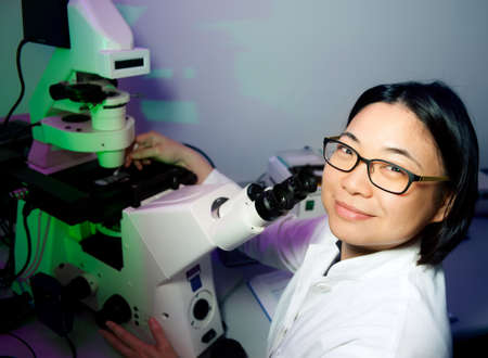technical service: Young oriental scientist works with modern inverted microscope Stock Photo
