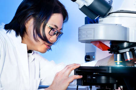 digicam: Young oriental scientist works with fluorescent microscope