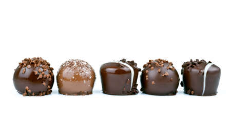 Row of chocolate truffles on white background  photo