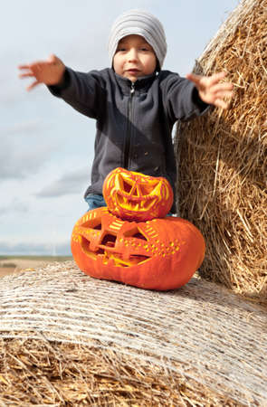 carved pumpkin: Boy and halloween pumpkins on roll of hay outdoors