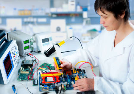 Tech tests electronic equipment in service centre Stock Photo - 15920371
