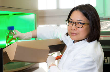 Oriental scientist next to bacterial incubator Stock Photo - 15940803