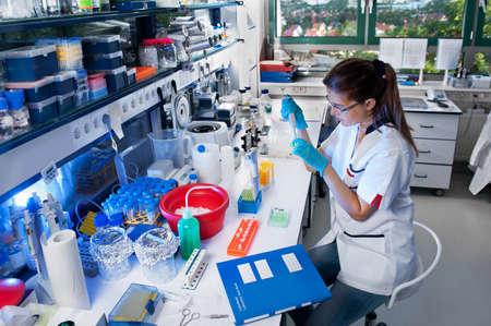 bata de laboratorio: Joven científico trabaja en el laboratorio biológico moderno