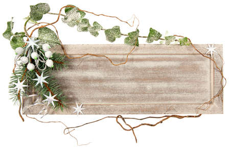 christmas decorations with white background: Wooden board decorated with ivy, spruce, stars and artificial berries
