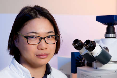 biopsy: Portrait of a young oriental scientist in a microscopic room Stock Photo
