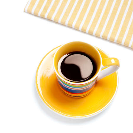 Yellow coffee cup and stripy linen on white background photo