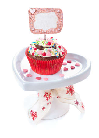 Cupcake with butter cream, sprinkles and empty caption on top, isolated on white photo
