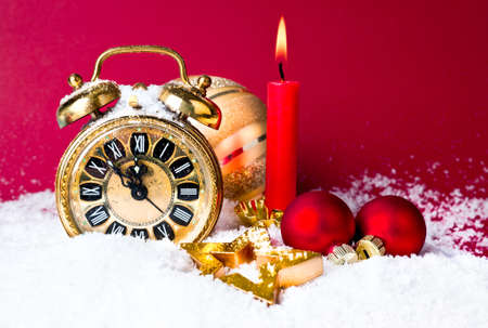 count down: Alarm clock set at five to twelve, xmas balls under snow and a candle on dark red background