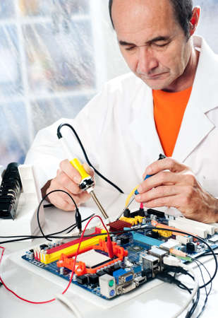 Senior male tech tests electronic equipment in service centre Stock Photo - 16986387
