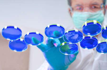 celula animal: Científico en el equipo de protección se encarga de las placas con el líquido azul Foto de archivo
