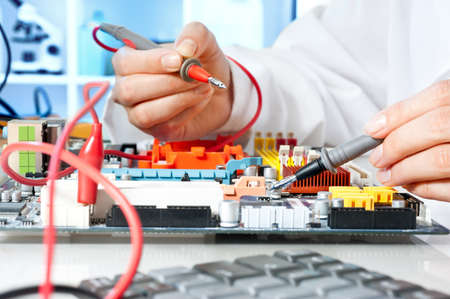 Tech tests electronic equipment in service centre Stock Photo - 17054272
