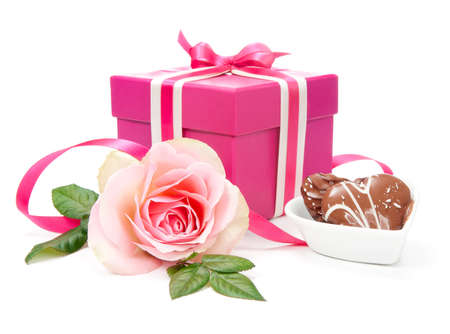 Pink gift box tied up with ribbons, heart chocolates and a rose on white background photo