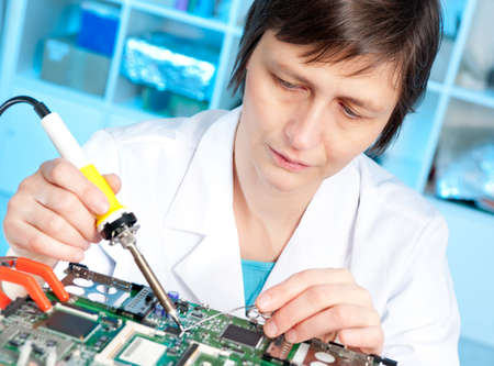 hardware repair: Tech tests electronic equipment in service centre