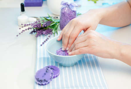 soaks: Client soaks her hands in a bowl of fragrant water before manicure