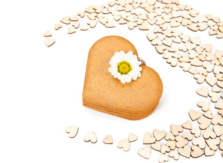 Stack of heart-shaped gingerbread cookies among smaller cardboard hearts photo
