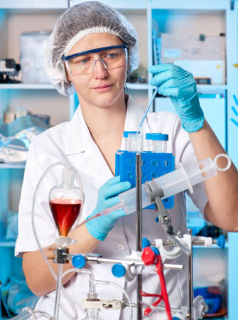 nitril: Senior female tech in protective wear works in chemical lab Stock Photo