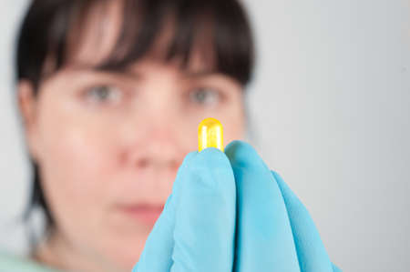 nitril: Closeup on gloved hand holding yellow capsule, copy space