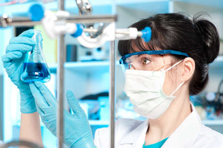 biotech: Female tech in protective wear works in chemical lab