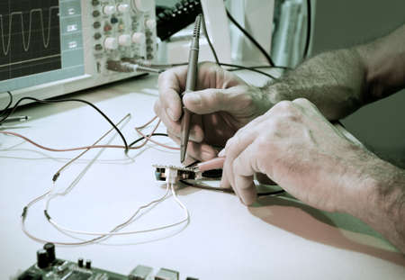 An engineer tests electronic components with oscilloscope in the service centre photo