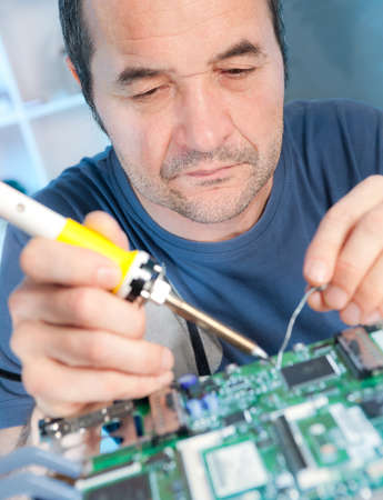 Senior male tech is soldering circuit board photo