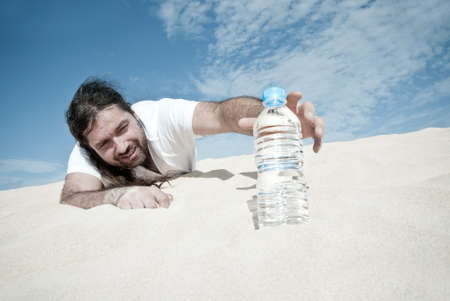 Thirsty man in the desert reaches for a bottle of water Stock Photo