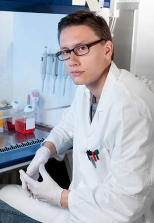 Cell culture laboratory, a young scientist by the sterile laminar photo
