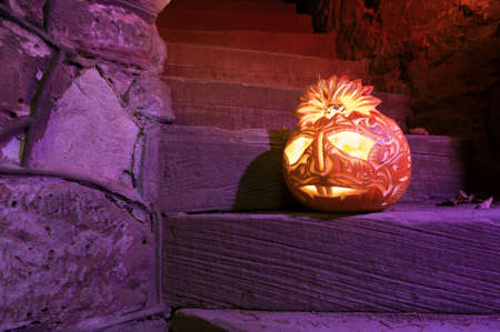 Halloween pumpkin with candle inside on purple-lit ancient staircase photo