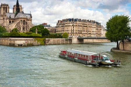 ile de la cite: Paris, France  Touristic boat on the river next to Ile de la Cite, with Notre Dame Cathedral visible on the right   Stock Photo