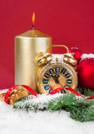 count down: New Year decorations  an old clock showing five to twelve, burning candle and winter decorations on red background, space Stock Photo