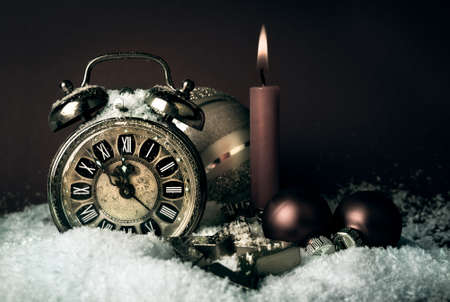 new year eve beads: Old alarm clock showing five to midnight and a candle on a  New Year Stock Photo
