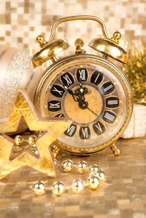 new year eve beads: Old clock on golden background set to five to twelve Stock Photo
