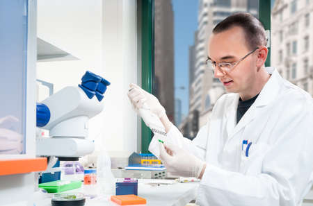 Young male scientist or student works in the lab photo