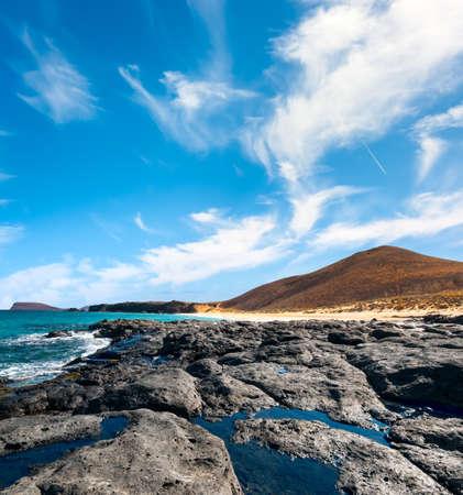 wild canary: Ancient lava stream goes into the ocean. Las Conchas bay, Graciosa, Canary Islands, Spain