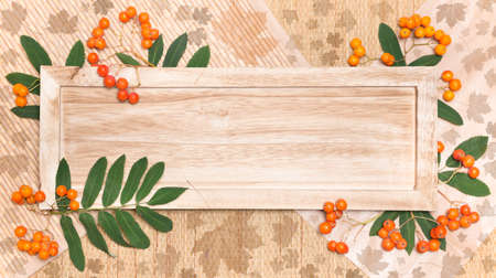 Wooden board on natural background decorated with Autumn rowan tree berries and leaves  Copy space photo