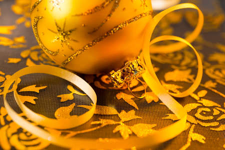 Closeup on golden Christmas ball on ornate organza background photo
