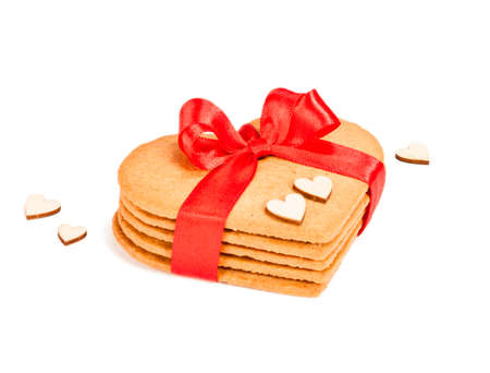 Geart-shaped gingerbread cookies tied up with red ribbon on white background photo