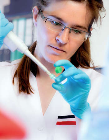 nitril: Portrait of a scientist with an automatic liquid dispenser in modern laboratory, shallow DOF
