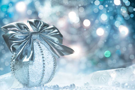 organza: Christmas bauble with silver bow on abstract background, text space