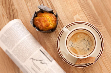 buisiness: Coffee, muffin and rolled buisiness newspaper