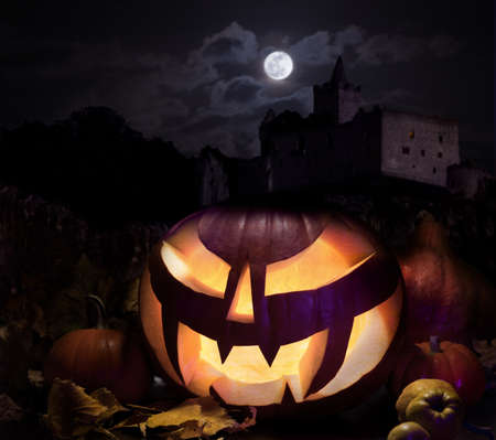 Halloween pumpkin with haunted castle under moonlight photo