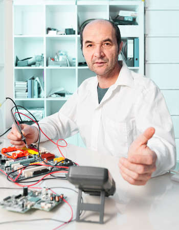 Senior repair tech assures you he fixes your electronic device Stock Photo - 22696568