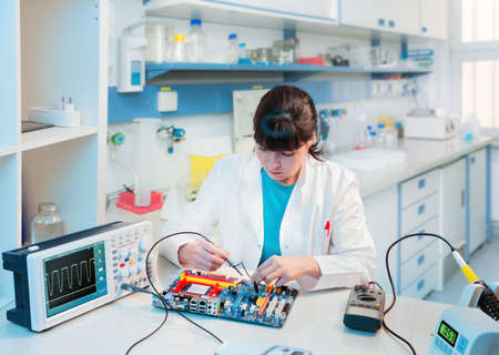 computer lab: Young scientist repairs electronic device in modern laboratory Stock Photo