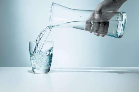 Pouring water from pitcher into a glass  版權商用圖片