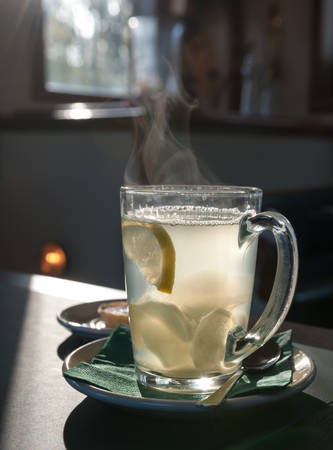 cold remedy: Winter hot drink with ginger and lemon in glass cup
