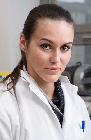 white coat: Young scientist, tech or PhD student in white coat looks at the camera Stock Photo