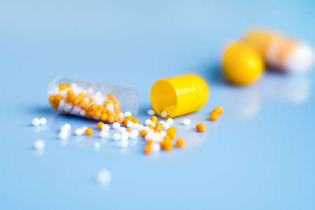 globular: Yellow capsules on blue , one split open Stock Photo