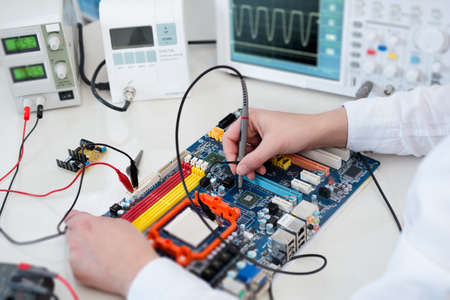 Female Tech tests electronic equipment in service centre